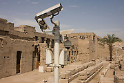 Modern CCTV security cameras keeping watch over the ancient Egyptian remains of Luxor Temple, Luxor, Nile Valley, Egypt.