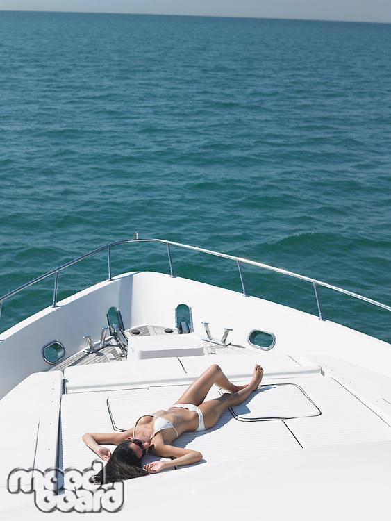 Young woman in bikini sunbathing on yacht elevated view
