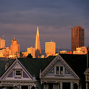 Painted Ladies Victorian Row Houses on Steiner Street with late afternoon light on San Francisco, California skyline in back