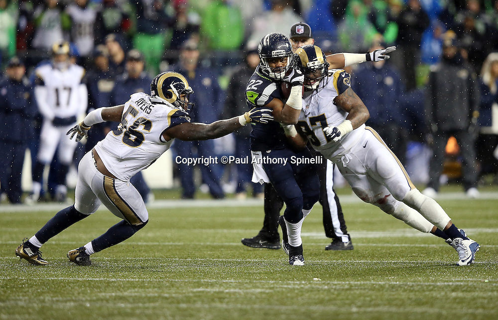Seattle Seahawks running back Fred Jackson (22) is hit by St. Louis Rams defensive end Eugene Sims (97) and St. Louis Rams outside linebacker Akeem Ayers (56) as he catches a fourth quarter pass good for a gain of 9 yards to the St. Louis Rams 26 yard line with about one minute left during the 2015 NFL week 16 regular season football game against the St. Louis Rams on Sunday, Dec. 27, 2015 in Seattle. The Rams won the game 23-17. (©Paul Anthony Spinelli)