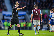 Andrew Madley (Referee) walking across to resolve a dispute during the Premier League match between Brighton and Hove Albion and Aston Villa at the American Express Community Stadium, Brighton and Hove, England on 18 January 2020.