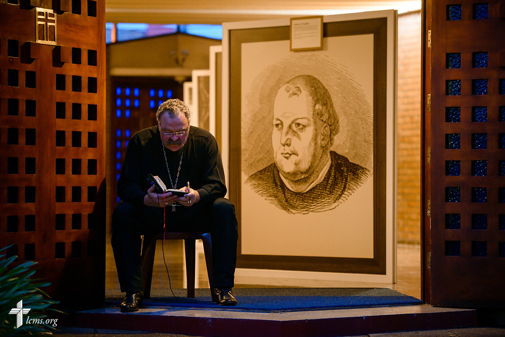 The Rev. Dr. Matthew C. Harrison, president of the LCMS, reads before evening service at Iglesia Luterana de Cristo Rey (Christ the King) in Guatemala City on Wednesday, Oct. 4, 2017, in Guatemala. Behind him is a display celebrating the 500th anniversary of the Lutheran Reformation. LCMS Communications/Erik M. Lunsford