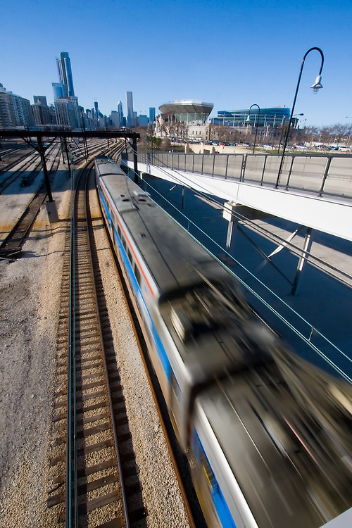 Streaking towards the city, a Metra Electric train passes the 18th St. station. In the background is Soldier Field and part of the Chicago skyline.