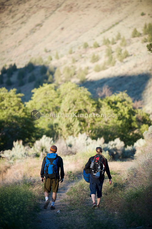 A young woman and mid adult man hiking with backpacks full of climbing gear at Trout Creek, Oregon. (Model Released)