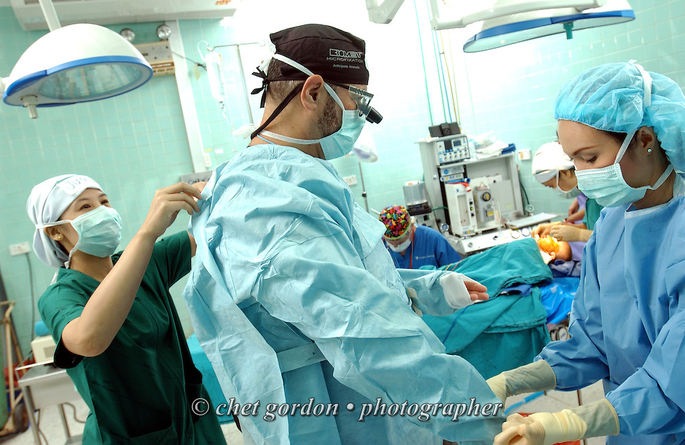 Venezuelan plastic surgeon Dr. Rafael Gottenger of Miami, FL is helped with his surgical gown prior to performing surgery on Khin Myint Noe, 9, at Mae Sot General Hospital in Mae Sot, Thailand on Monday, November 12, 2007.  © Chet Gordon for Operation Smile