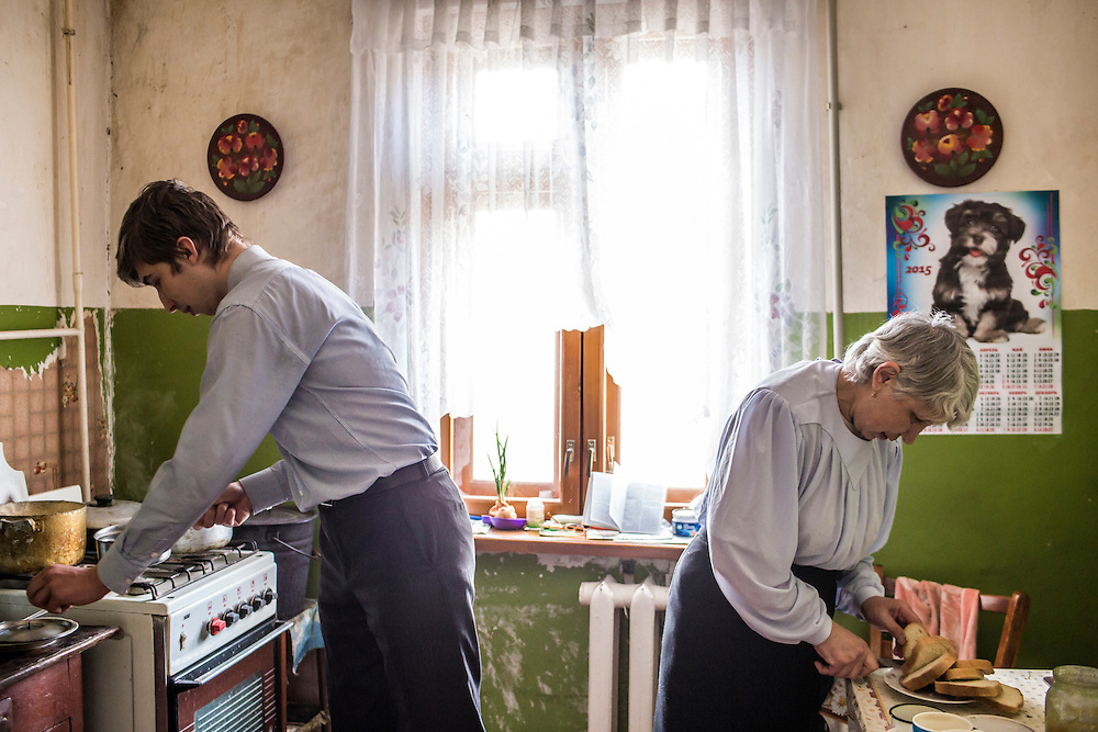 LUHANSK, UKRAINE - MARCH 15, 2015: Pavel Pavlov, left, prepares tea with his mother Valentina at her apartment in Luhansk, Ukraine. CREDIT: Brendan Hoffman for The New York Times