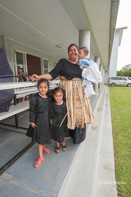 Tongan family leaving Sunday service at King's Church, Nuku'alofa, Kingdom of Tonga, South Pacific, dressed in Sunday best, including ta'ovala ( pandanus mat )