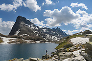 A female hiker at the lake Geisspfadsee with the peaks of the Rothorn and the Schwarzhorn, Landschaftspark Binntal, Valais, Switzerland