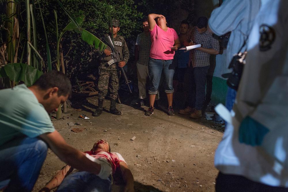 San Pedro Sula, Honduras<br /> <br /> Juan 27, sk&ouml;ts med ett flertal skott framf&ouml;r sin mammas hem. Han var deporterad fr&aring;n USA f&ouml;r ett par m&aring;nader sedan.<br /> P&aring; bilden gr&aring;ter hans mamma och syskon i bakgrunden.<br /> <br /> Photo: Niclas Hammarstr&ouml;m