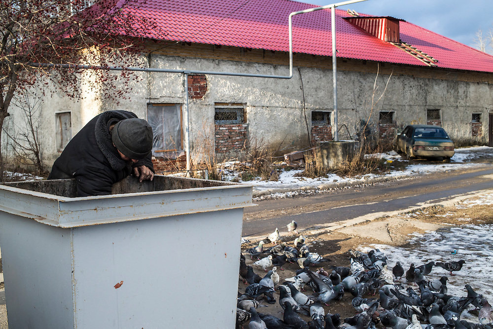 A man digs through a dumpster to find food scraps to feed to pigeons on Saturday, November 30, 2013 in Asbest, Russia.