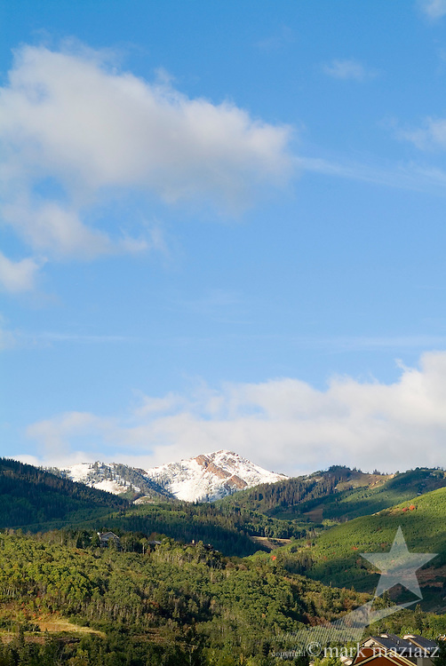 large late summer scenic of Jupiter Peak with snow and small luxury homes in foreground