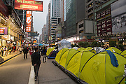 Walking past tents erected along the busy Nathan Rd in Mong Kok. Protesters known as the Umbrella Revolution or Occupy Mongkok, an extension of the larger Occupy Central movement, have taken over a number of blocks on the busy road and staged an ongoing demonstration calling for universal suffrage for Hong Kong.
