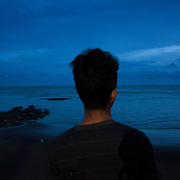 It is 5 am and Joseph inspects the surf of the sea. The previous night was stormy and the tide is still coming in so even though the sea looks calm and the wind has died down breaking through the surf will be tough. <br />