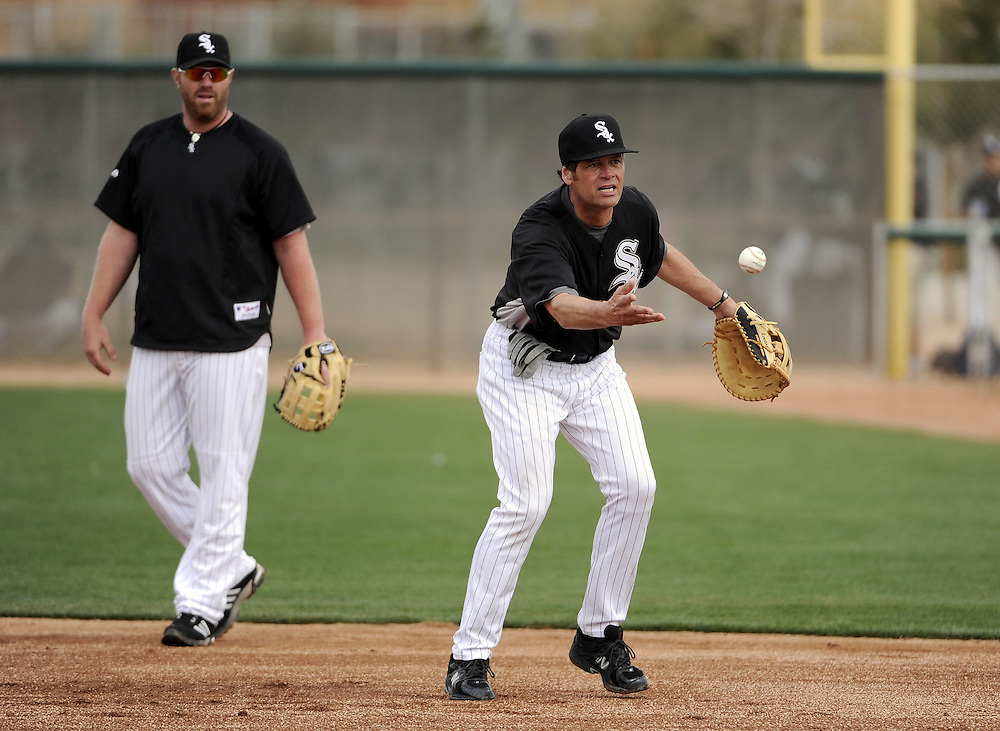 GLENDALE, AZ - FEBRUARY 26:  NASCAR driver Michael Waltrip takes infield practice as Adam Dunn #32 of the Chicago White Sox looks on during a spring training workout on February 26, 2011 at Camelback Ranch in Glendale, Arizona. (Photo by Ron Vesely)