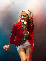 Low angle view of young woman singing into microphone