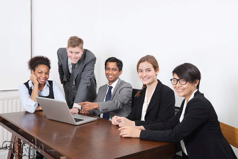 Portrait of multiethnic professionals using laptop at conference room