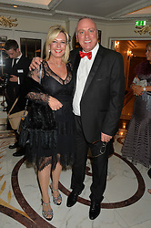 Status Quo band manager NEIL WARNOCK and his wife CHRISTINE at the David Shepherd Wildlife Foundation 30th anniversary Wildlife Ball at The Dorchester, Park Lane, London on 10th October 2014.