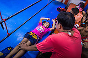 """18 DECEMBER 2104 - BANGKOK, THAILAND: A girl who wants to box does sit up exercises on the apron of the ring at the Kanisorn gym. The Kanisorn boxing gym is a small gym along the Wong Wian Yai - Samut Sakhon train tracks. Young people from the nearby communities come to the gym to learn Thai boxing. Muay Thai (Muai Thai) is a Thai fighting sport that uses stand-up striking along with various clinching techniques. It is sometimes known as """"the art of eight limbs"""" because it is characterized by the combined use of fists, elbows, knees, shins, being associated with a good physical preparation that makes a full-contact fighter very efficient. Muay Thai became widespread internationally in the twentieth century, when practitioners defeated notable practitioners of other martial arts. A professional league is governed by the World Muay Thai Council. Muay Thai is frequently seen as a way out of poverty for young Thais and Muay Thai camps and schools are frequently crowded. Muay Thai professionals and champions are often celebrities in Thailand.     PHOTO BY JACK KURTZ"""