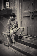 A young boy sits outside his home in Bangalore, India