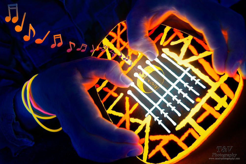 Musical notes float from a kalimba  played by someone with glowing jewelry.Black light