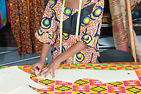 Midsection of female fashion designer tracing pattern on cloth with chalk