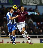 Photo: Chris Ratcliffe.<br />West Ham United v Wigan Athletic. The Barclays Premiership. 28/12/2005.<br />Bobby Zamora (R) of West Ham goes head to head with Arjan de Zeeuw of Wigan.