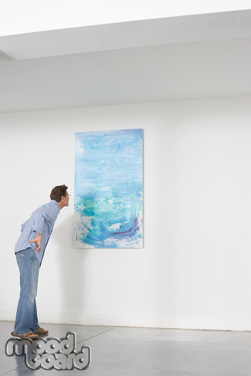 Man contemplating paintings in gallery