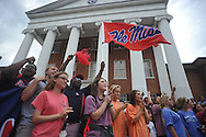 Blair Smith waves an Ole Miss flag as the ESPN College Gameday bus pulls in front of the Lyceum, in Oxford, Miss. on Thursday, October 2, 2014.