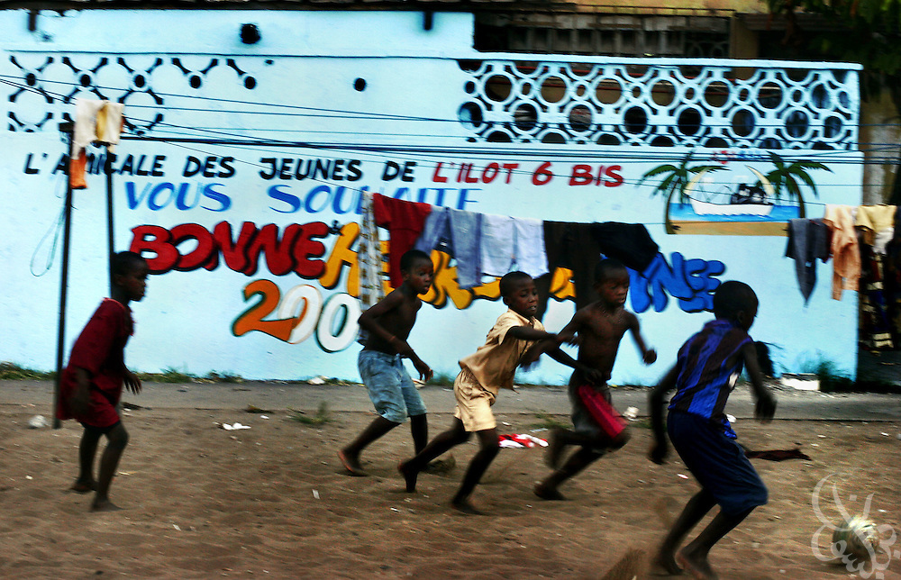 Poor, barefoot Ivorian children play football on a dirt pitch in the Port Bouet neighborhood of Abidjan, Ivory Coast February 17, 2006.  Ivorian children grow up dreaming of becoming players for Ivorian pro clubs, the national team, or in the European leagues.