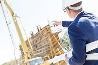 Rear view of architect holding blueprints while pointing at construction site