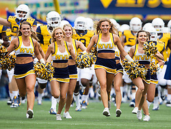 Sep 12, 2015; Morgantown, WV, USA; The West Virginia cheerleaders run out on the field before the start of their game against the Liberty Flames at Milan Puskar Stadium. Mandatory Credit: Ben Queen-USA TODAY Sports