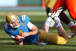 Dec 31, 2011; San Francisco CA, USA; UCLA Bruins quarterback Kevin Prince (4) is knocked to the ground against the Illinois Fighting Illini during the second quarter at AT&T Park. Illinois defeated UCLA 20-14. Mandatory Credit: Jason O. Watson-US PRESSWIRE