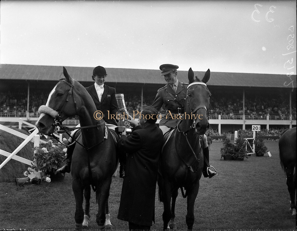 """03/08/1960<br /> 08/03/1960<br /> 03 August 1960<br /> R.D.S Horse Show Dublin (Wednesday). Mr. Kevin Boland T.D. Minister for Defence presenting the Hunting Horn Award (presented by the Irish Department of Defence) to Mrs Dawn Wofford on """"Hollandia"""" and Captain W.A. Ringrose on """"Loch an Easpaig"""", joint first prize-winners of the Epreuve de Puissance International Jumping Competition at the Dublin Horse Show."""