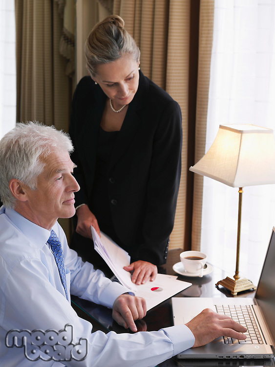 Business man using laptop business woman sitting on desk looking at documents elevated view