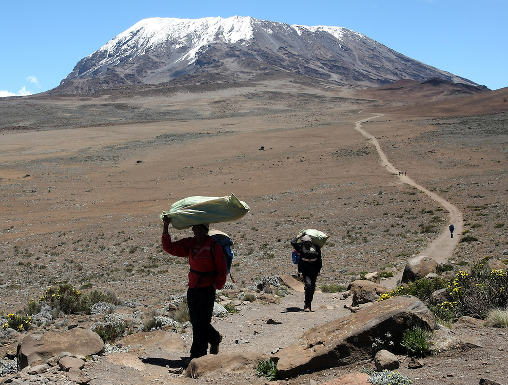 On their way back down the mountain, porters carry the gear of their climbers across The Saddle of Mt. Kilimanjaro, with the majestic summit in the background. For those on the way up, the toughest part of the climb still lies ahead.