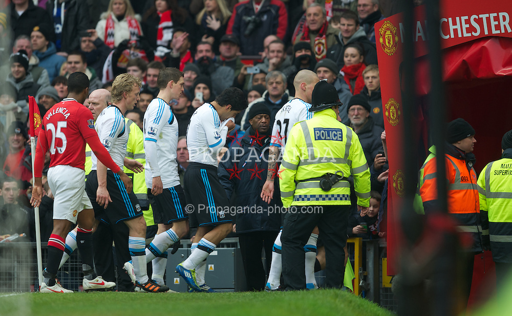 MANCHESTER, ENGLAND - Saturday, February 11, 2012: Liverpool's Luis Alberto Suarez Diaz is protected by his team-mates as Manchester United protest to the referee as the players head to the tunnel at half-time during the Premiership match at Old Trafford. (Pic by David Rawcliffe/Propaganda)