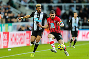 Pierre-Emile Hojbjerg (#23) of Southampton clears the ball away from Joelinton (#9) of Newcastle United during the Premier League match between Newcastle United and Southampton at St. James's Park, Newcastle, England on 8 December 2019.