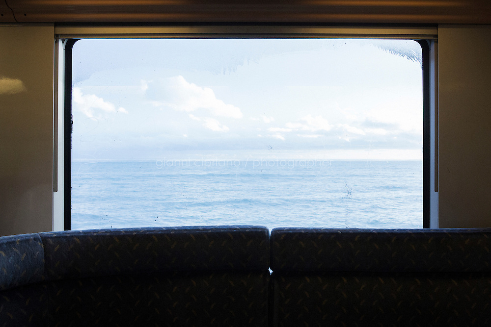 MENTON, FRANCE - 17 NOVEMBER 2014: A view of the Mediterranean Sea of the Côte d'Azur (French Riviera) from the train that goes from Ventimiglia to Nice, taken by migrants that want to cross the border from Italy to France, in Menton, France, on November 17th 2014. The Ventimiglia-Menton border is the border between Italy and France crossed by migrants who decide to continue their journey up north towards countries such as Germany, Sweden, The Netherlands and the UK where the process to receive the refugee status or humanitarian protection is smoother and faster.