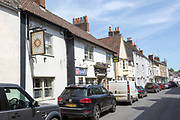 Historic buildings in main street of Bruton, Somerset, England, UK,  The Sun Inn public house sign