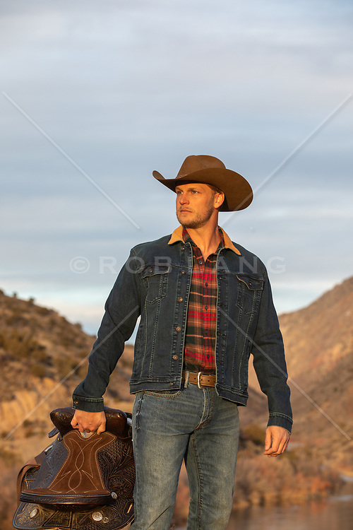 cowboy with a saddle at sunset