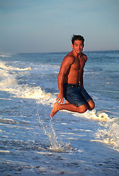 Man in mid air jumping above the waves  while making a funny face
