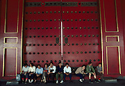 People resting against door at The Forbidden City, China