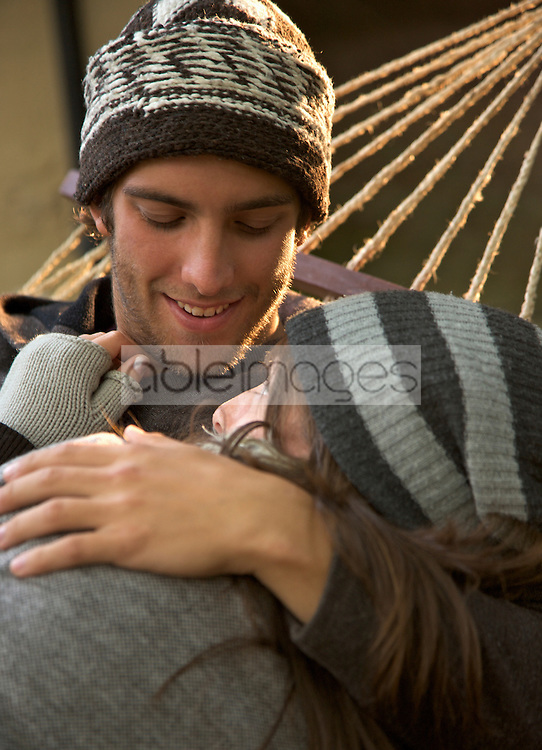 Young couple lying on hammock embracing and looking at each other