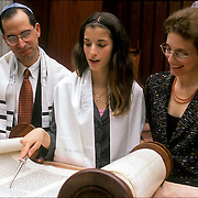 Parents with Bat Mitzvah girl in synagogue reading from the torah scrol, ceremony admitting Jewish girl as an adult into Jewish Community at age 13 in a conservative temple in South Orange, NJ. <br /> <br /> Maya Salz Gering - Bat Mitzvah on  11-15-03