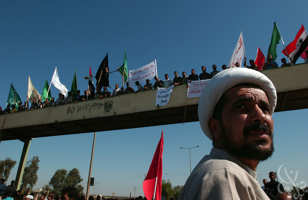 An Iraqi Shia cleric keeps a watchful eye on U.S. soldiers gathering nearby during an October 07, 2003 protest against the detention of local Shia Imam Mo'ayed al-Khezragi by U.S. military  at the al-Baya'a mosque in Baghdad, Iraq.