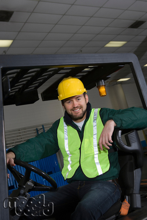 Cheerful man sitting on fork lift truck