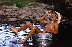 cowboy taking an outdoor bath in a bucket placed in a stream