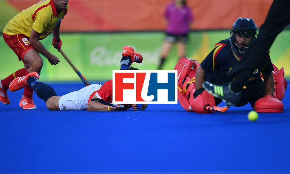 Great Britain's Mark Gleghorne (C) fails to score past Spain's Quico Cortes (R) during the mens's field hockey Britain vs Spain match of the Rio 2016 Olympics Games at the Olympic Hockey Centre in Rio de Janeiro on August, 12 2016. / AFP / MANAN VATSYAYANA        (Photo credit should read MANAN VATSYAYANA/AFP/Getty Images)