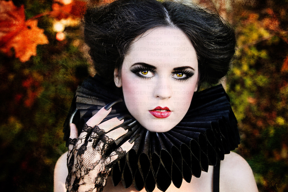 A girl with pale skin, black hair and heavy make-up, wearing a baroque style black collar and black lave gloves looking at the camera.