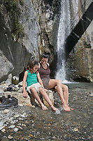 Mother and daughter (10-12) sitting on rock by river
